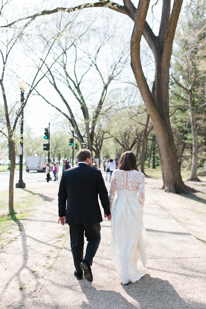 Holding hands and walking down the sidewalk to the Tidal Basin for more wedding photos