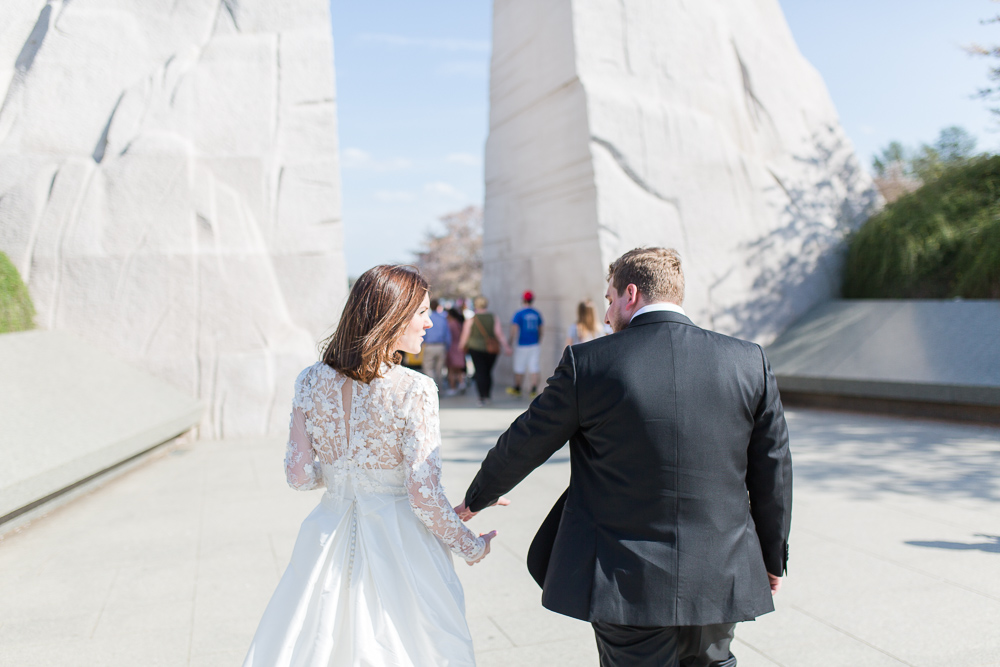 Bride and groom holding hands in front of the Martin Luther King Jr Memorial | Candid DC Wedding Photographer | Wedding dress by Rue de Seine from Lovely Bride, Rochester NY