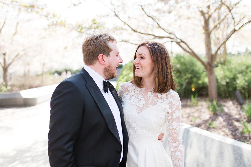 Bride and groom having fun walking through the cherry blossom trees in Washington, DC | Megan Rei Photography | Fun Wedding Photographer in DC