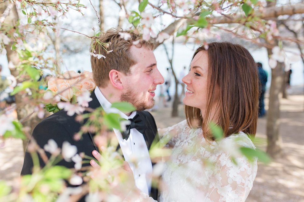 Bride and groom smiling at each other next to the cherry blossom trees | Best Locations in DC for Wedding Pictures