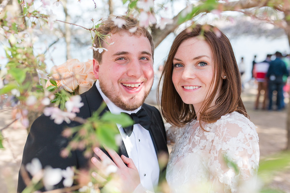 Happy picture of the wedding couple at the Tidal Basin with the cherry blossom trees | Cherry Blossom Wedding Photos | Megan Rei Photography