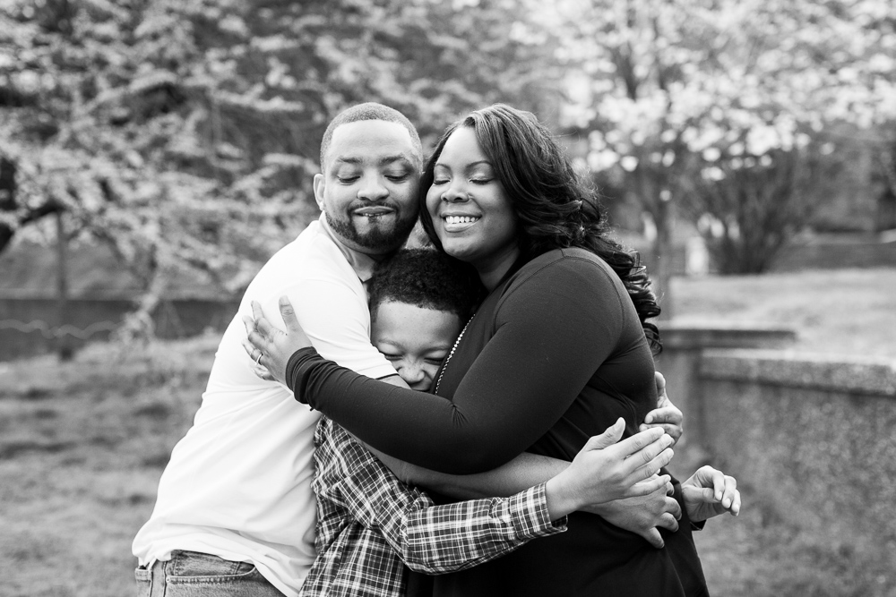 Family hug during spring engagement session in Washington, DC | DC Documentary Photographer