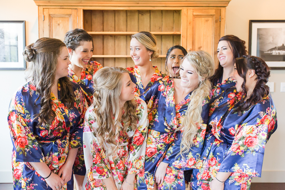 Bride with bridesmaids in matching robes while getting ready at King Family Vineyards