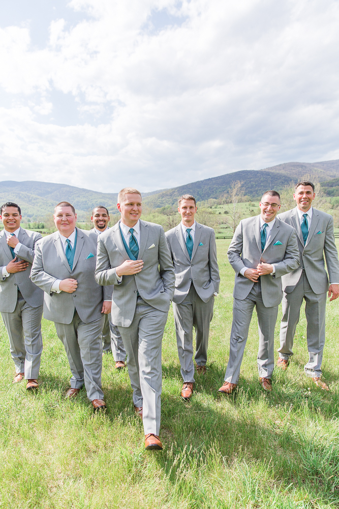 Groom walking through the field with his groomsmen | Candid Crozet Wedding Photographer