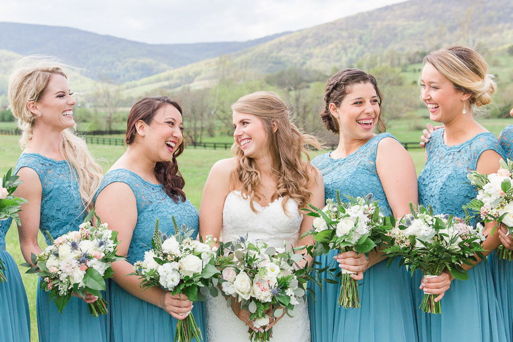 Bride smiling with her bridesmaids in teal dresses at a King Family Vineyards wedding