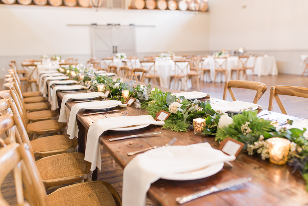 Wooden farm table with greenery garland at the King Family Vineyards Carriage House | Rustic Wedding Venues near Charlottesville, VA