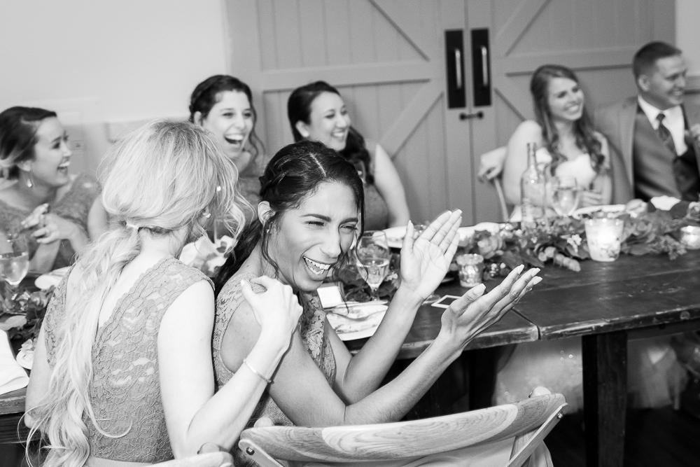 Bridesmaids laughing during the wedding speeches at King Family Vineyards | Crozet Wedding Venue