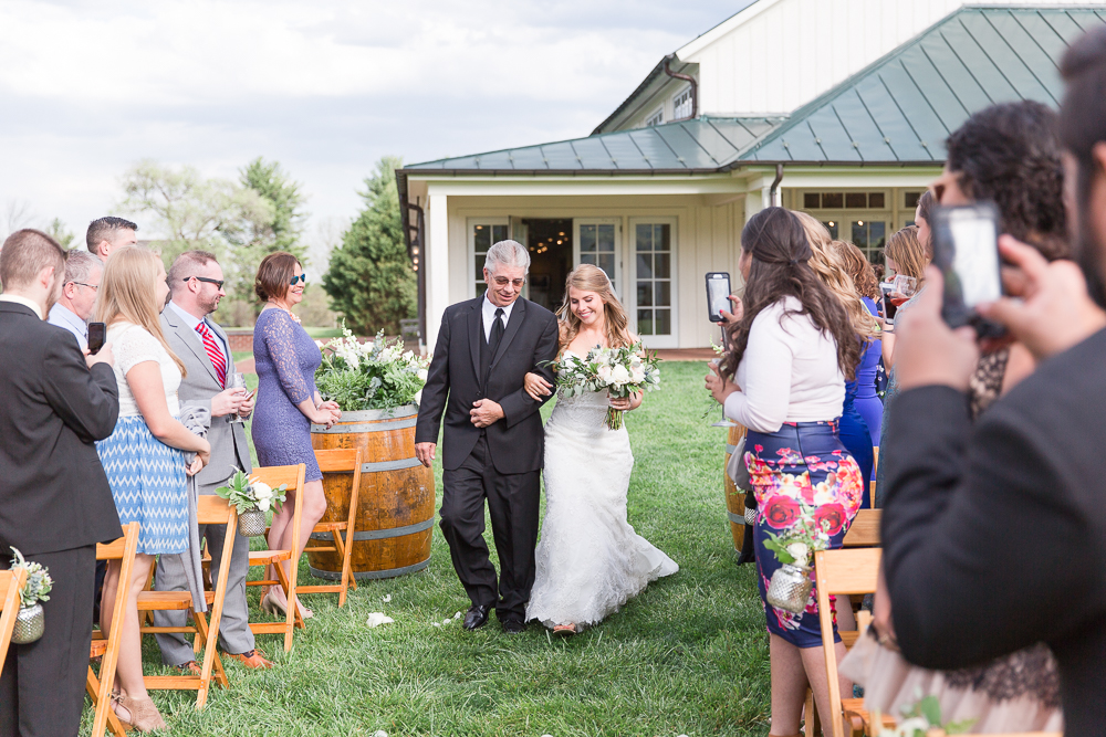 Bride and her dad walking down the aisle during wedding ceremony at King Family Vineyards | Candid Charlottesville Photographer