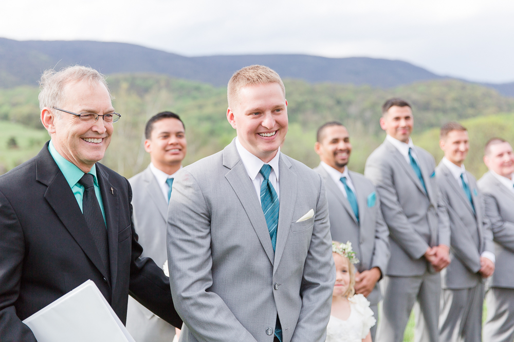 Happy groom looking at the bride at the beginning of their wedding ceremony at King Family Vineyards | Candid Charlottesville Wedding Photography