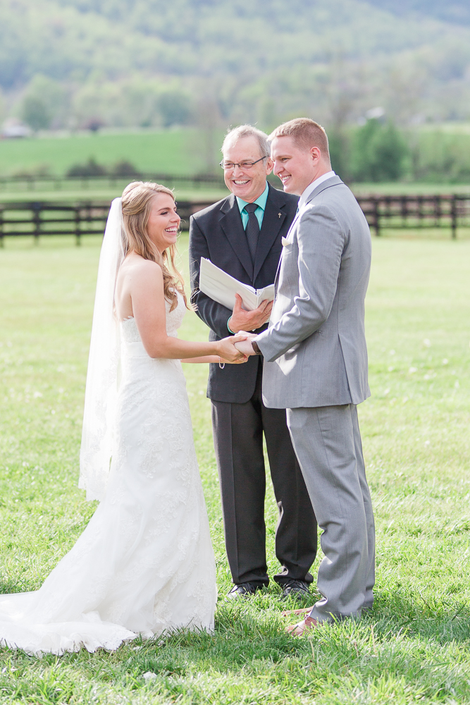 Candid picture of bride and groom laughing during their wedding ceremony at King Family Vineyards | Documentary Wedding Photography