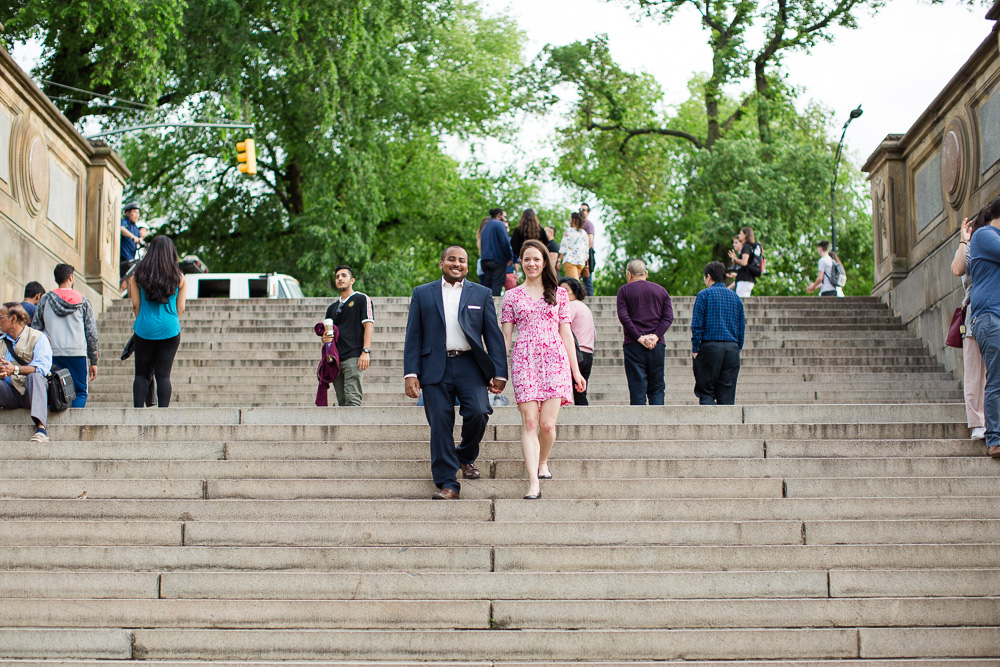 Walking down the big staircase at the Bethesda Terrace during a Central Park engagement session | Best NYC Engagement Picture Locations