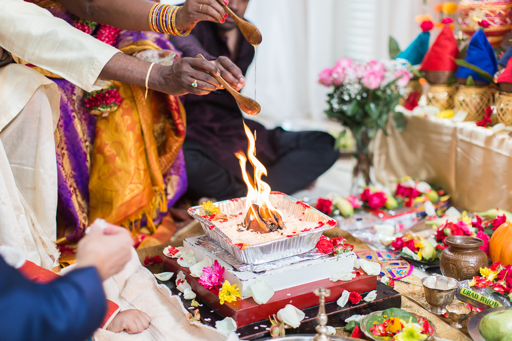 Pouring honey during fire ritual of the Shashti Poorthi | Hindu Wedding Ceremony Photography
