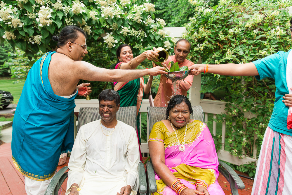 Pouring holy water over the bride and groom during Hindu marriage ceremony in Northern Virginia