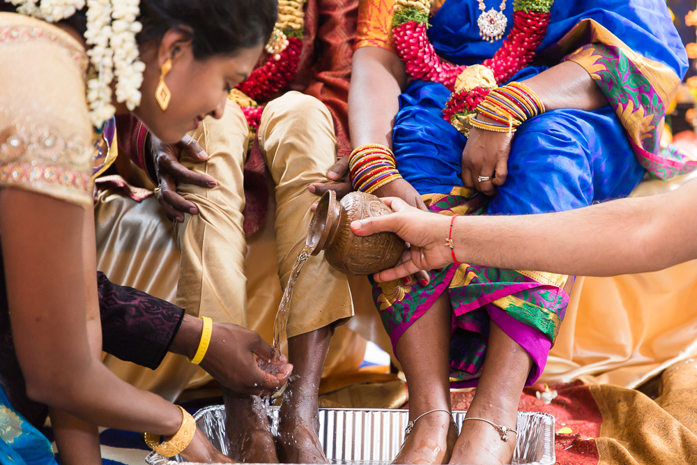 Children pouring water over their parents' feet during Indian marriage ceremony