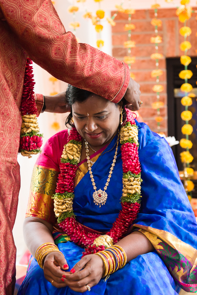 Husband placing necklace on wife during Hindu Shashti Poorthi in Herndon