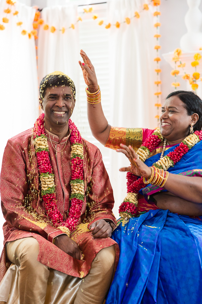 Wife pouring rice over her husband's head during Indian vow renewal in Northern Virginia
