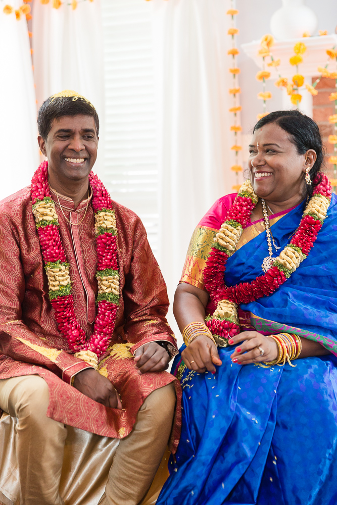 Candid picture of bride and groom laughing during Indian ceremony