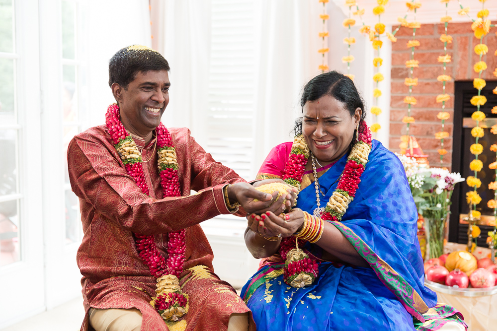 Wedding couple laughing while exchanging handfuls of rice