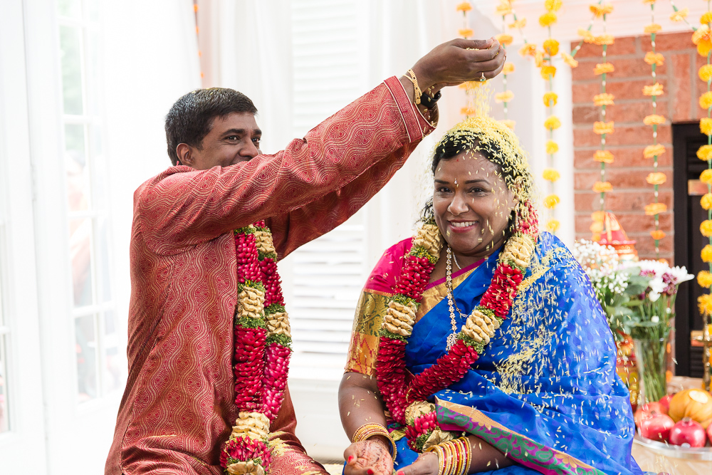 Husband pouring rice over wife's head during fun marriage ceremony near DC
