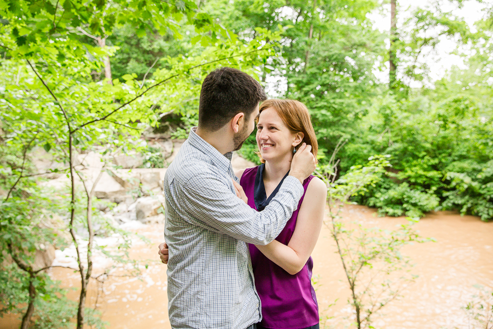 Smiling at each other during forest engagement pictures