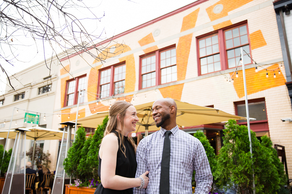Engaged couple looking at each other near the Love mural in Eastern Market