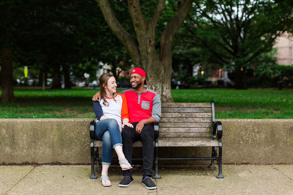 Engaged couple sitting on the bench at Lincoln Park in Washington, DC
