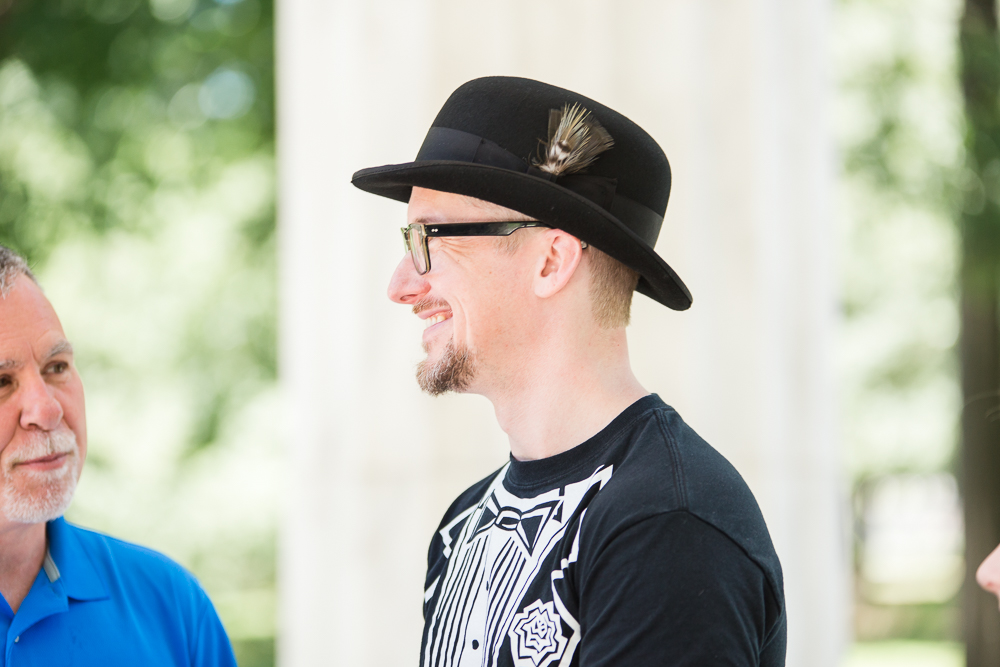 Groom wearing a tuxedo t-shirt and black hat during his wedding ceremony at the DC War Memorial