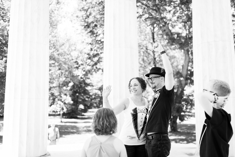 Bride and groom waving to the passing tourists along the National Mall after their alternative wedding ceremony