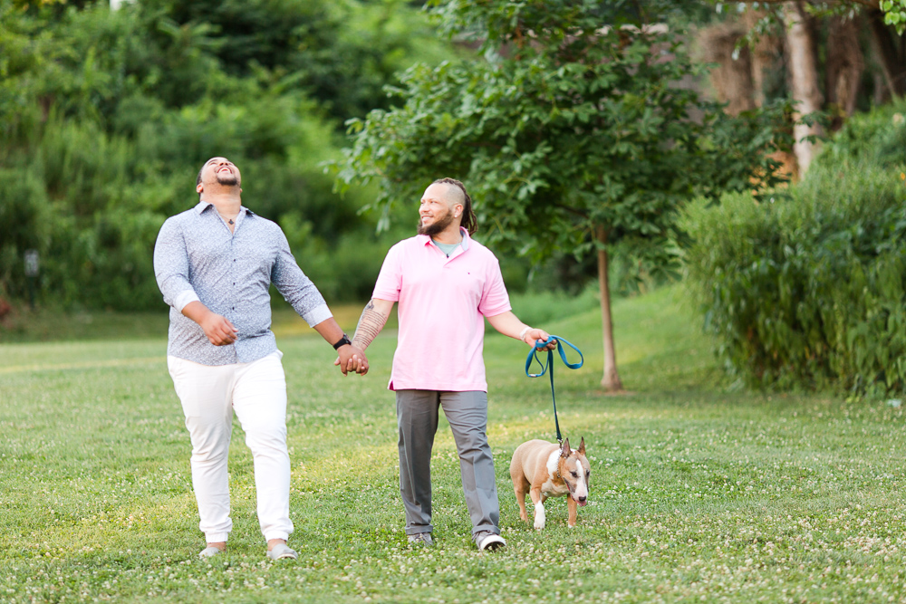 Candid photo of gay couple walking through a field with their dog in Alexandria