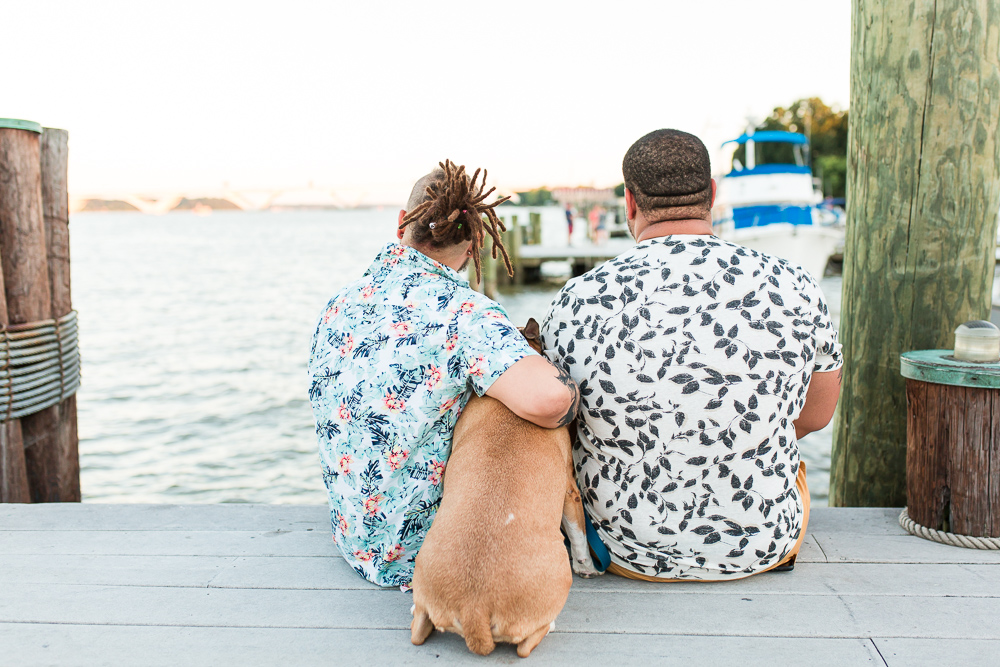 Gay couple with their dog, sitting on the dock and looking at the Potomac River