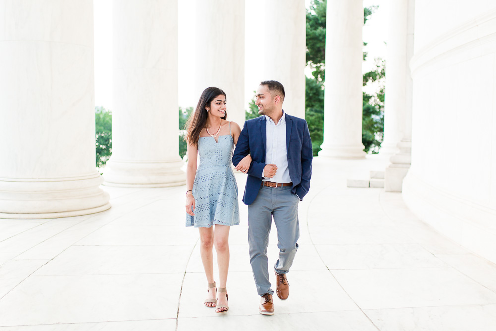 Walking arm in arm by the white columns of the Jefferson Memorial | Best Washington DC Engagement Locations