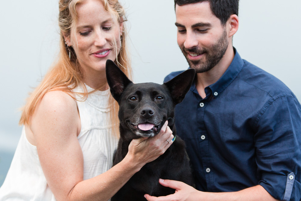 Happy dog with her engaged parents during their adventurous engagement shoot