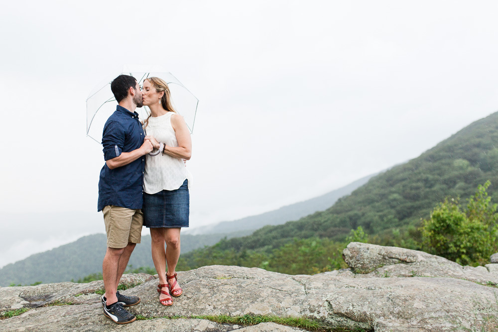 Kissing under an umbrella on the rocks off of Skyline Drive | Luray Virginia Photographer