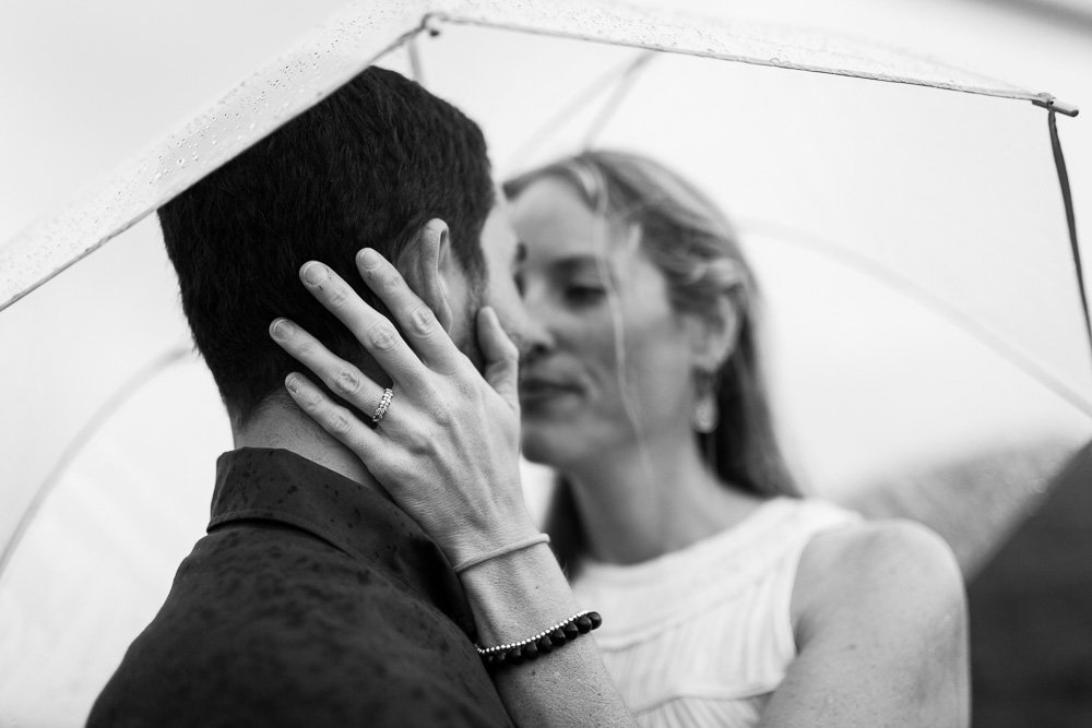 Leaning in for a kiss | Romantic engagement pictures in the rain
