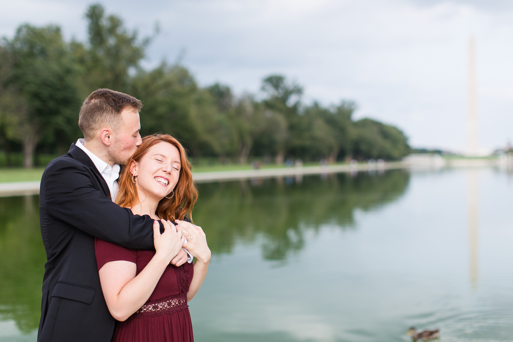 Giving his fiance a kiss on the head during their engagement session at the monuments
