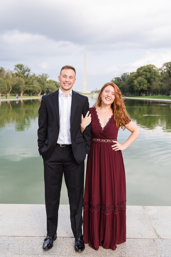 Engaged couple posing for their engagement pictures in front of the Reflecting Pool and Washington Monument | Washington, DC engagement photographer
