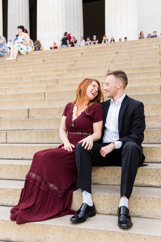 Candid engagement photo sitting on the steps of the Lincoln Memorial