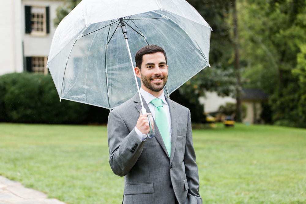 Groom waiting for the bride with his umbrella | Rainy wedding day in Leesburg, Virginia