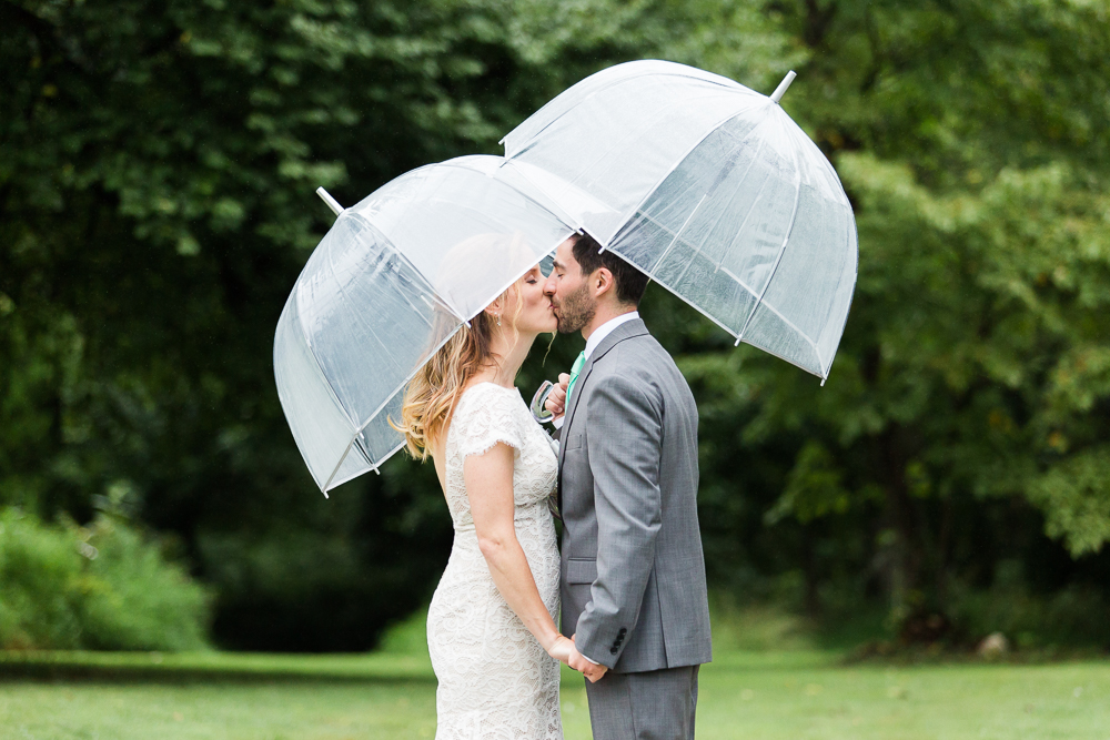 Rainy wedding day kiss under umbrellas