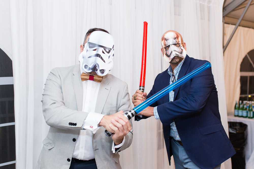 Wedding guests playing with Star Wars masks and light sabers in the photo booth