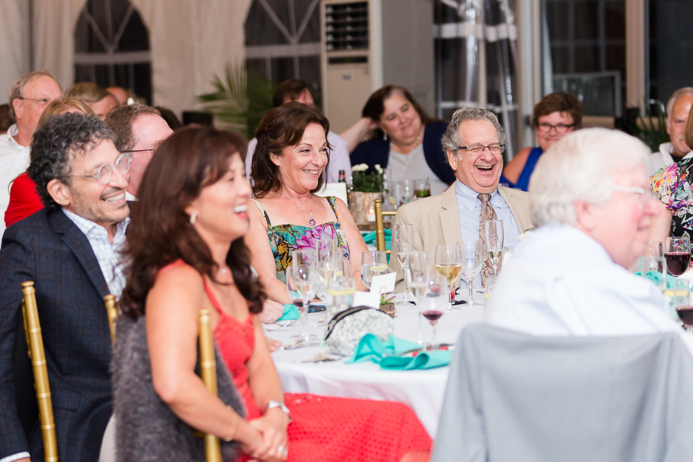 Wedding guests laughing during the toasts