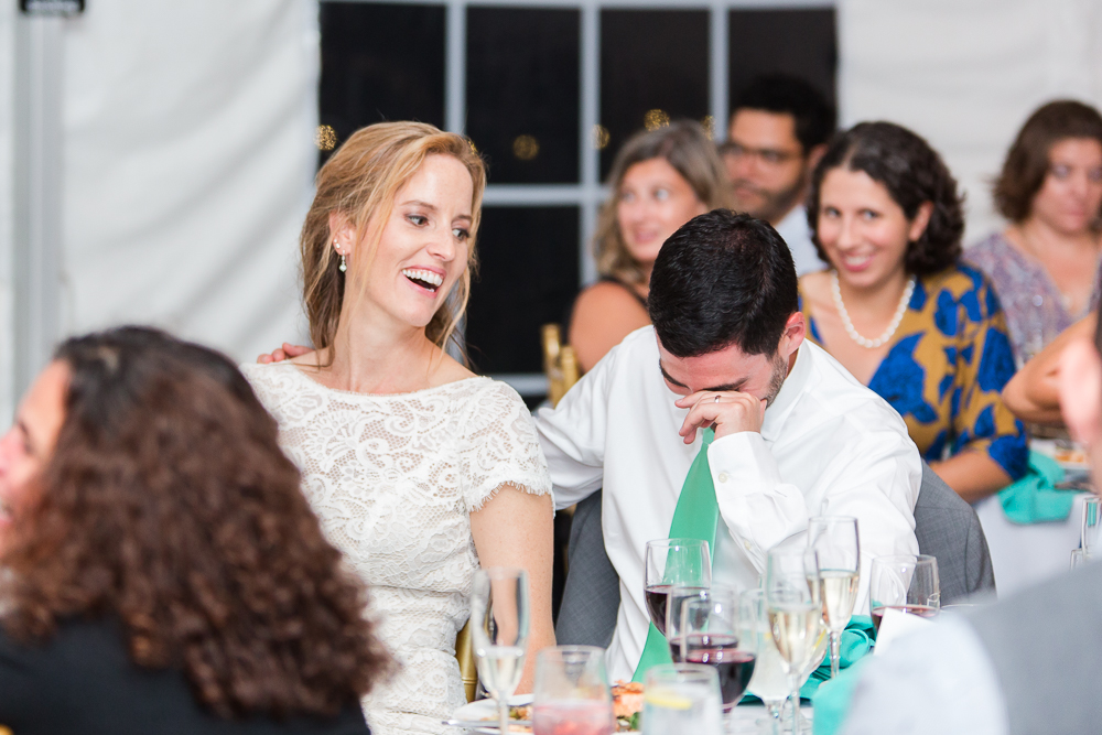 Candid laughter from the bride and groom during their Rust Manor House wedding reception