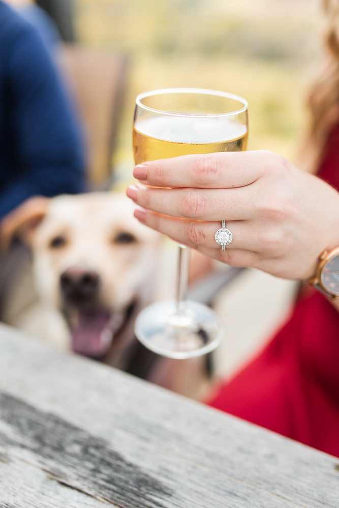 Halo engagement ring with wine glass during engagement session at Blue Valley Vineyard