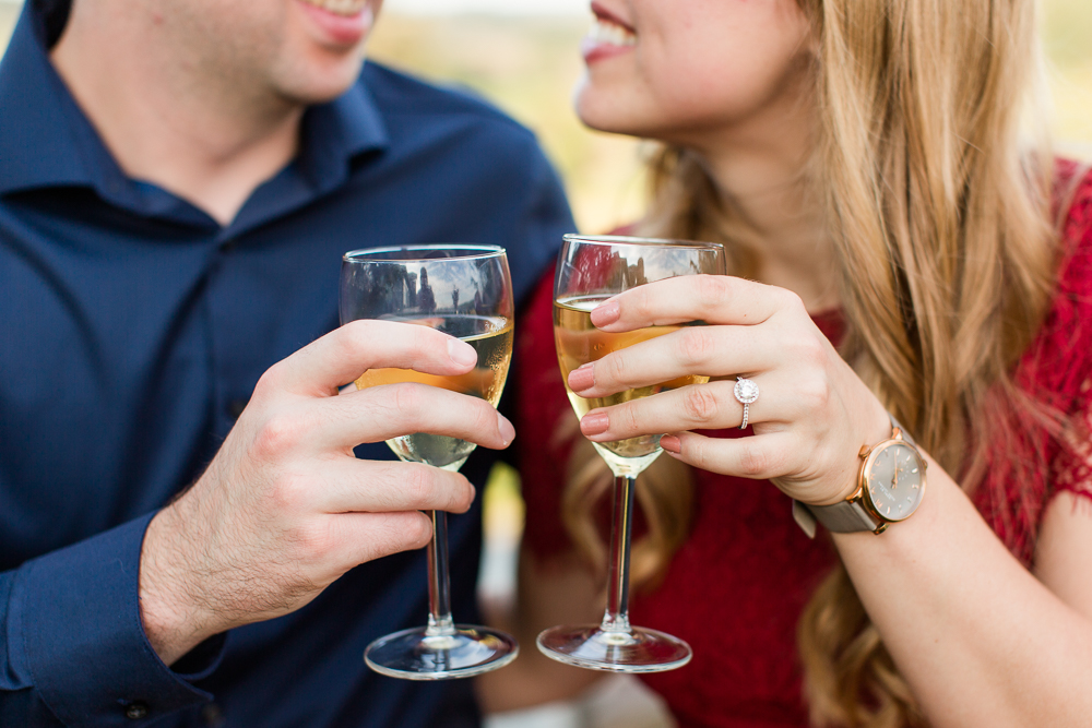 Engagement picture with halo engagement ring and wine glasses