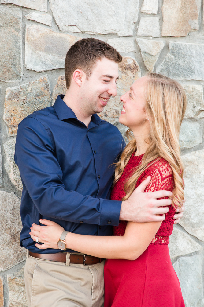 Engagement photo in front of stone wall at the winery
