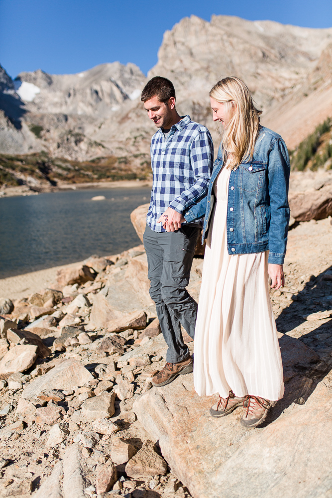 Candid photo of couple holding hands and hiking across the rocks