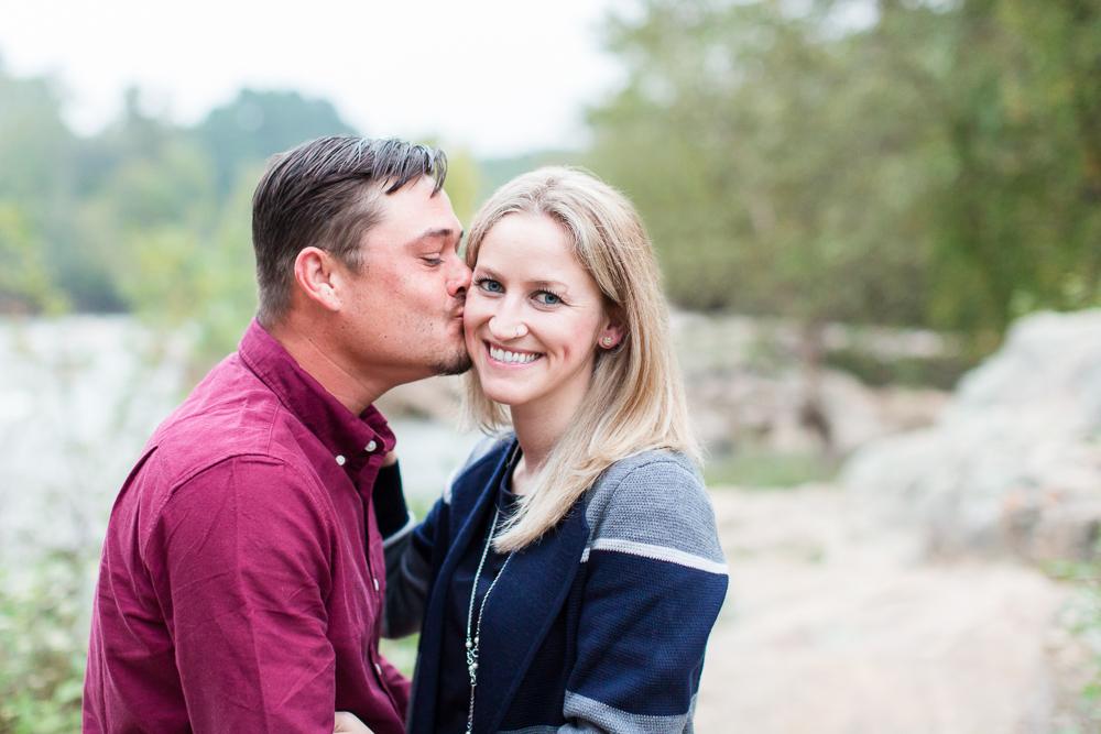 A kiss on the cheek by the Rappahannock River in Fredericksburg, Virginia | Fredericksburg engagement photographer