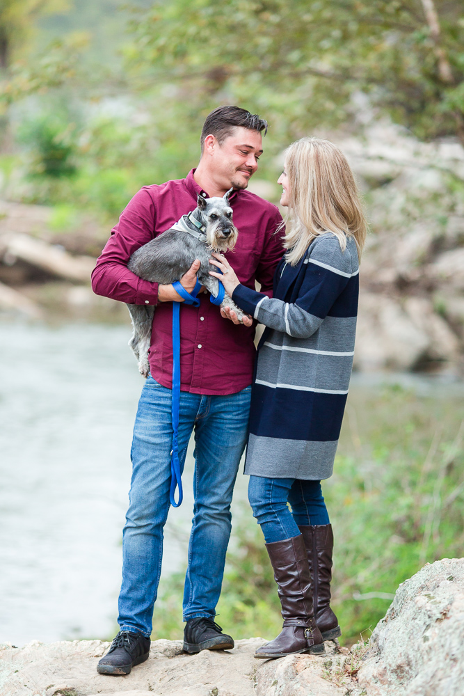 Engaged couple holding their miniature schnauzer during a portrait session in Fredericksburg, Virginia