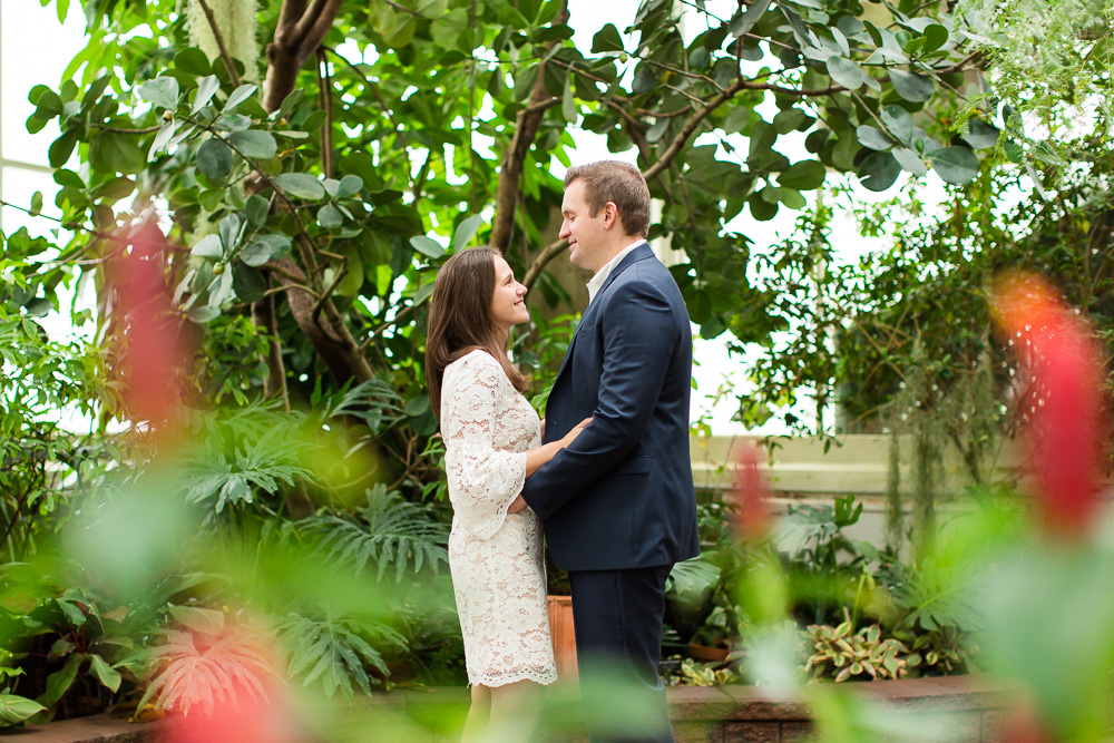 Engagement picture through the plants in the botanical gardens in Buffalo, NY