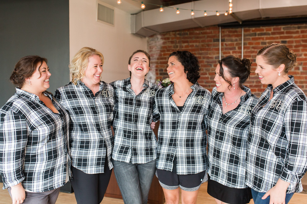 Bride and bridesmaids in matching plaid shirts, laughing while getting ready before the wedding ceremony at Loft at 600 F